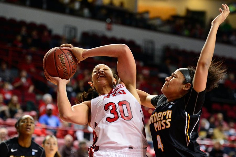 The Hilltoppers' Chastity Gooch is fouled by Southern Miss' Tamara Jones during Saturday's game at Diddle Arena in Bowling Green. Southern Miss defeated WKU, 63-61.