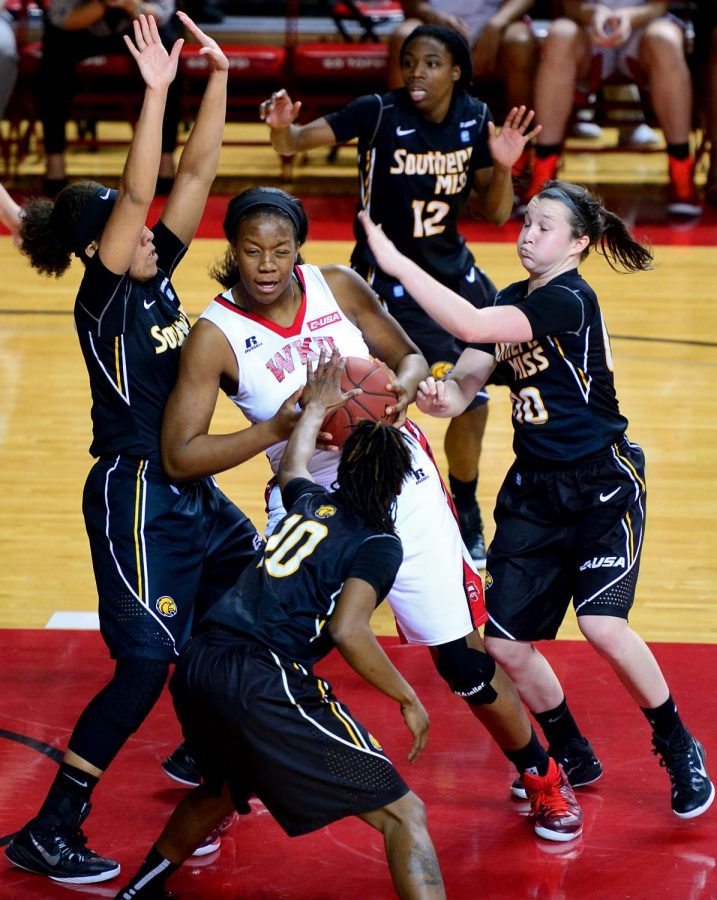 WKU forward Bria Gaines maneuvers through the lane against Southern Mississippi defenders during on January 31, 2015. WKU lost with a final score of 63-61.
