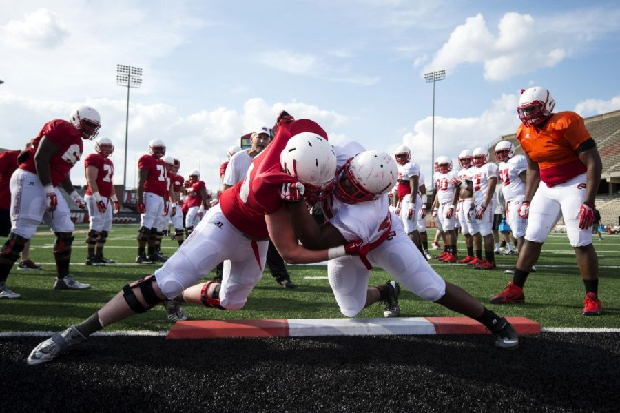 Offensive lineman Matt Nord, #69, left, practices a drill with teammate, Julien Lewis, #96, defensive lineman, right, during a football practice at L.T. Smith Stadium on WKUs campus on March 25, 2014. EMILY KASK/ Herald