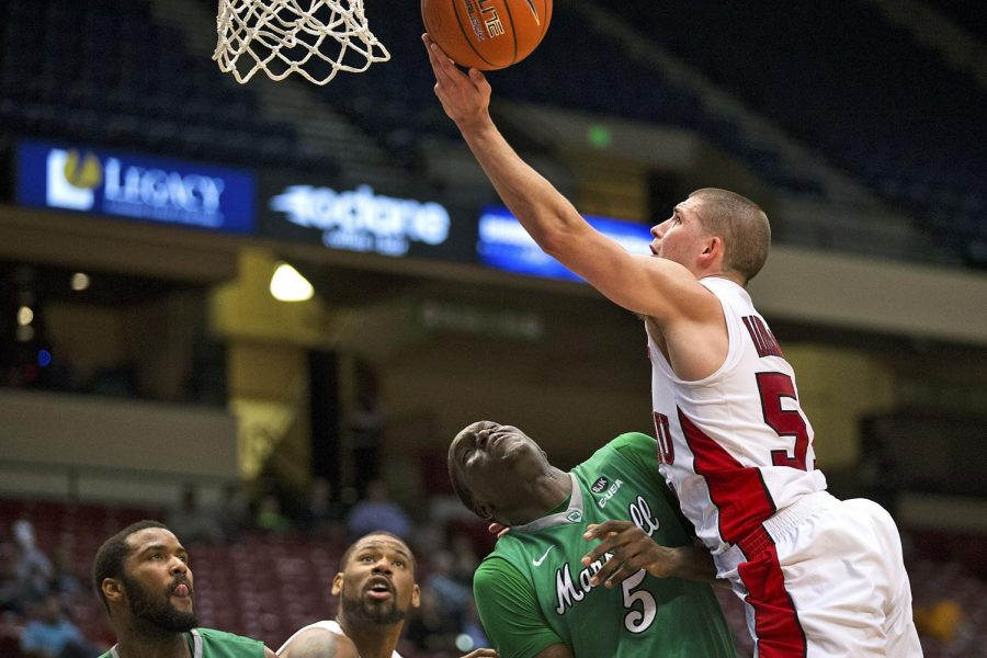 WKU redshirt sophomore guard, Chris Harrison-Docks (51), shoots a layup and draws a foul from Marshalls forward Cheikh Sane (5) during the Toppers 59-45 win in the first round of the Conference USA tournament Wed. March 11, 2015, at Legacy Arena in Birmingham, Ala. Harrison-Docks led the Hilltoppers playing forty minutes and scoring 18 points in the game. WKU will take on the University of Alabama at Birmingham at 6 p.m. Thursday, March 12, 2015. Mike Clark/HERALD