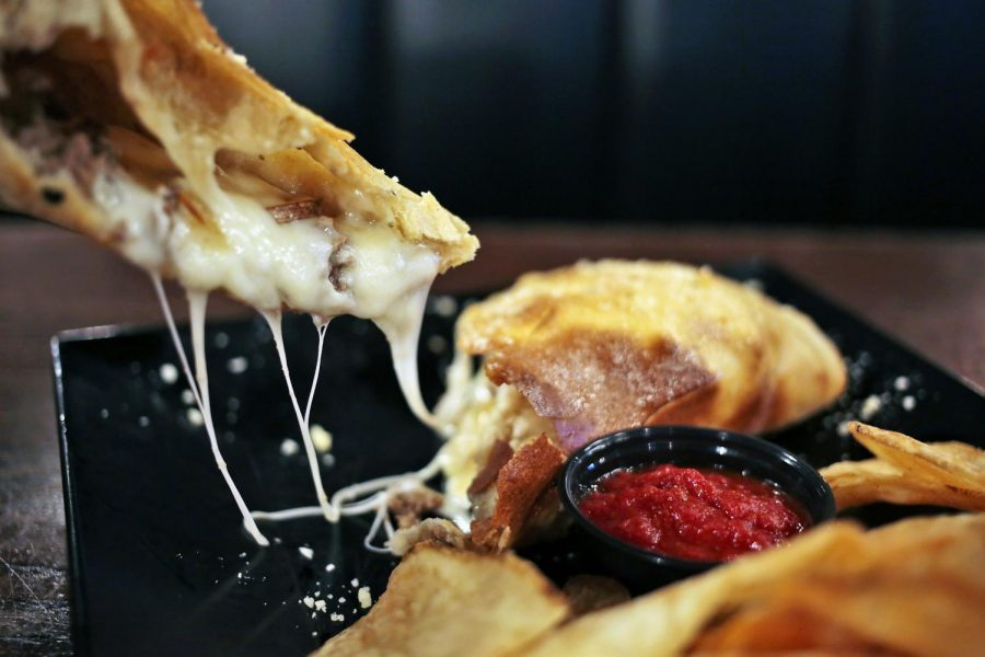 A calzone filled with mushrooms, onions, ground beef and cheese is served with house cut chips and marinara sauce at Lost River Pizza Company at 2440 Nashville Road. Leanora Benkato/HERALD