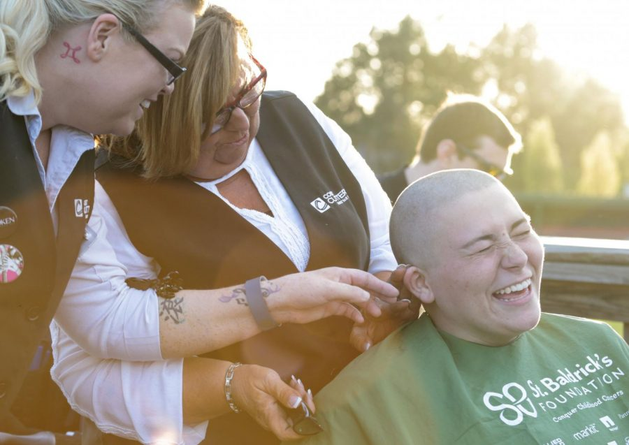 Gabbi Hagan, Tompkinsville senior, laughs because her head is ticklish while Debbie Vincent and her daughter Jessica Vincent inspect Debbie's head-shaving work. Hagan, who is the Mental Health Committee Head of Omega Phi Alpha, has shaved her head three times for St. Baldrick's. During the event, Vincent, the operational manager at Cost Cutters inside Walmart on Campbell Lane, shared a story with the audience about a young member of her family who passed away from childhood cancer. Omega Phi Alpha hosted St. Baldrick's on Saturday April 11, 2015, at the Nick Denis Field after the WKU Baseball game. Volunteer stylists shaved the heads and cut the hair of student who raised money for childhood cancer research. The cut hair, if it was long enough, was also donated to organizations which make wigs for children.