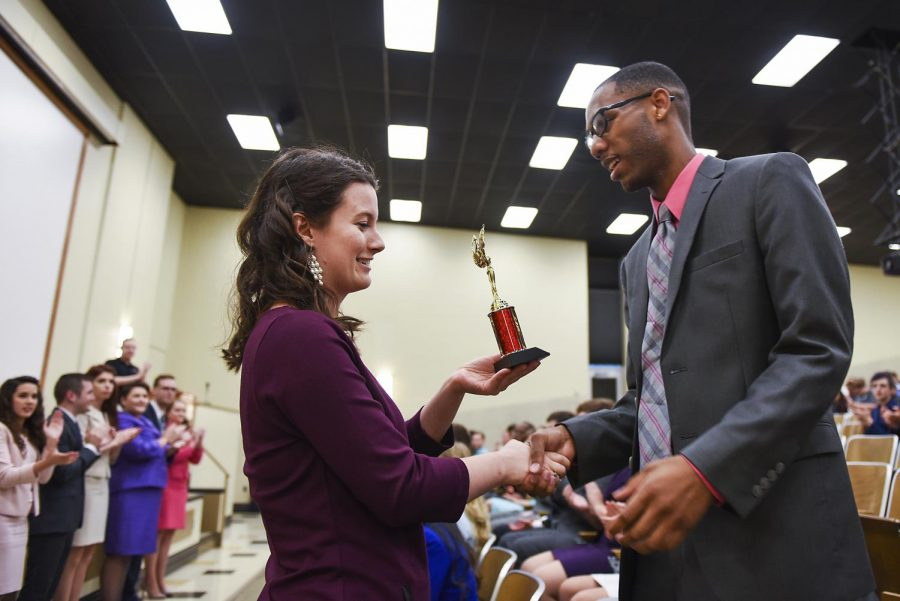 WKU senior and forensics team member Paige Settles, left, presents Bryan Sonnier, a student at William Carey University, right, the Top Novice award for the forensics after-dinner speaking category during the Forensics Fiesta closing ceremony in Grise Hall Sunday. This weekend, students from 24 universities competed in the invitational competition, which took place in the Garrett Conference Center.