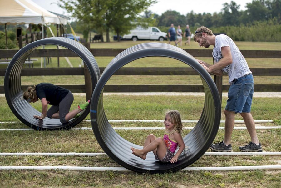Tim Pennington, right, of Cave City plays with his daughters, four-year-old Khloe Pennington, center, and 11-year-old Adrianna Pennington, left, Saturday at Jackson's Orchard. The Penningtons visited the orchard to pick apples and play on the playground.