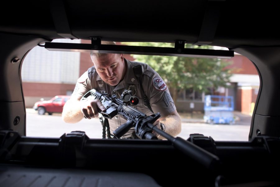 WKU+police+Sgt.+Benjamin+Craig+examines+his+Double+Star+AR15+rifle%2C+equipped+with+red+dot+sight%2C+fore-grip%2C+silencer+and+flashlight+in+the+back+of+his+service+truck+on+campus+Wednesday.+Craig+has+worked+for+the+university+for+seven+years+and+openly+supports+the+campus+gun+policy.+%22As+long+as+people+are+being+safe%2C+that%27s+the+bottom+line%2C%22+Craig+said.%C2%A0