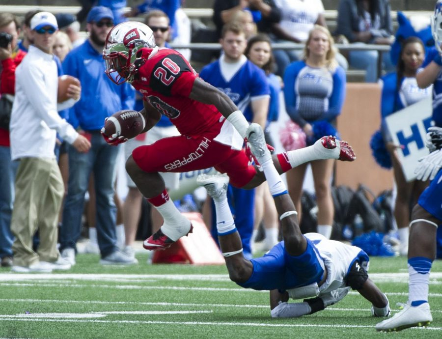 WKU%27s+running+back+Anthony+Wales+%2820%29+hurdles+a+Middle+Tennessee+defender+during+the+Hilltoppers%27+58-28+win+Saturday+at+Houchens+Industries+-+L.T.+Smith+Stadium.