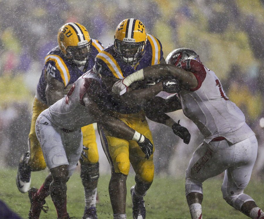 WKUs linebacker, Dejon Brown, 17, right, and defensive linemen, Kalvin Robinson, 48, tackle LSUs running back, Leonard Fournette, 7, during the Hilltoppers 48-20 loss Saturday at Tiger Stadium in Baton Rouge, La.