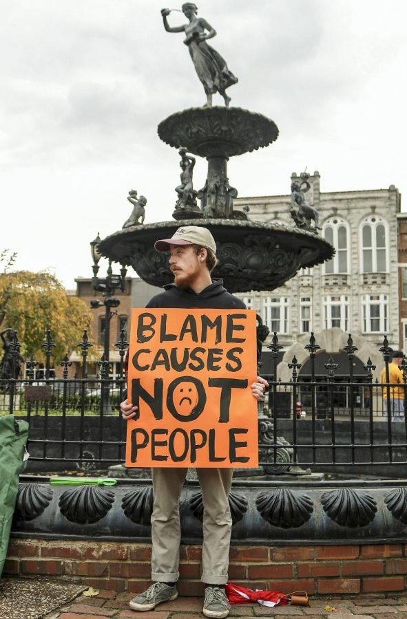 Freshman Devin Beach of Louisville demonstrates by holding a sign that brings awareness to homelessness during a protest at Fountain Square Park Saturday. The protest was put together by junior Maura Broderson of Versailes and featured a mixed crowd of supporters and individuals affected by homelessness. Tyger Williams/Special to the Herald