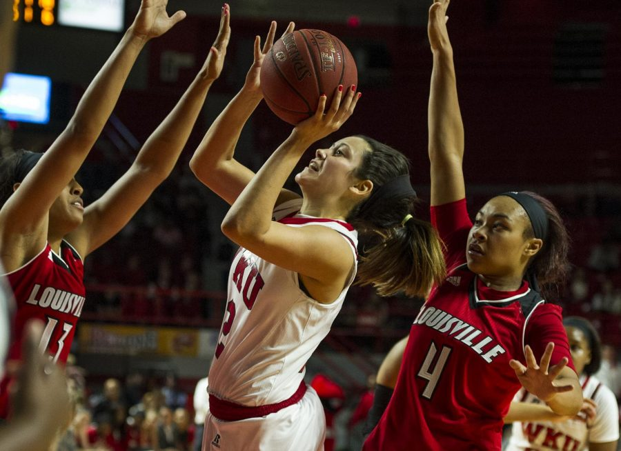 WKU's guard Kendall Noble (12) shoots the ball from between Louisville forward Cortnee Walton (13) and forward Mariya Moore (4) during the Lady Topper's 71-69 win Saturday at E.A. Diddle Arena.
