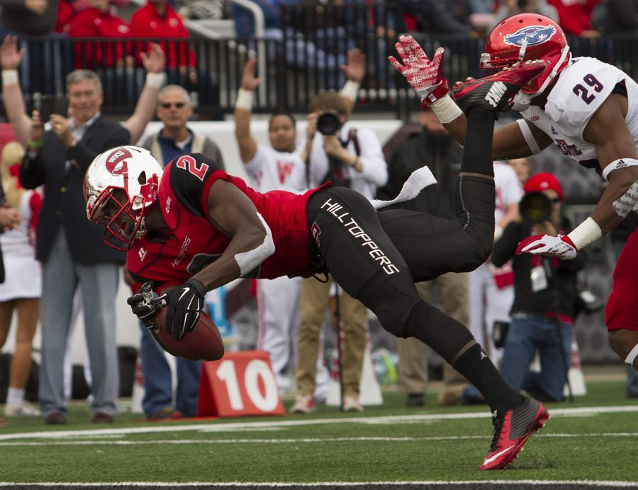 WKUs wide receiver Taywan Taylor (2) tumbles and dives to catch a touchdown pass as Florida Atlantic Universitys defensive back Sharrod Neasman (29) attempts to cover him during the Hilltoppers 35-19 win Saturday at Smith Stadium.