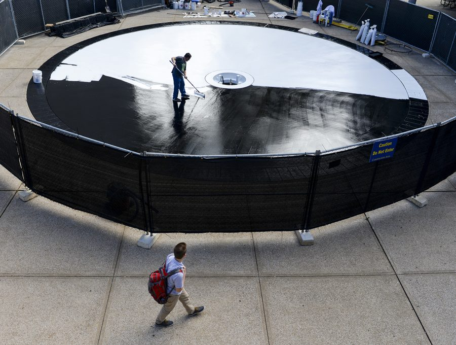 John Silliman applies primer for the fountain renovation Monday outside Helm Library. Katie Roberts/HERALD