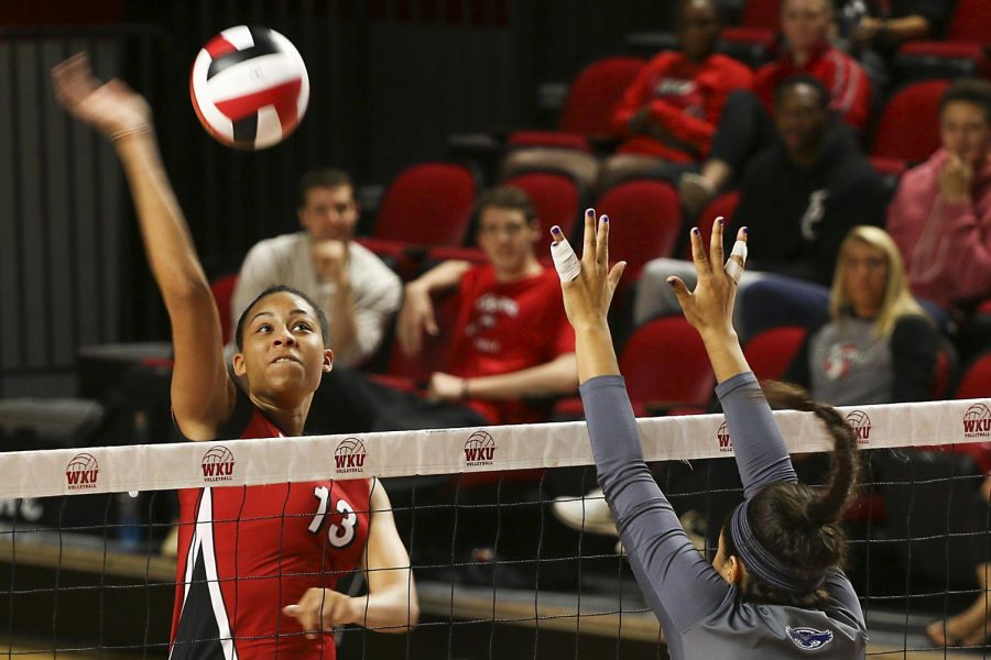 Senior middle hitter Noelle Langenkamp (13) spikes the ball against freshman middle blocker Gabriela Martin (2) during WKUs match against Florida Atlantic on Sunday, Oct. 25. The Lady Toppers won In three sets. Tyger Williams/Special to the Herald