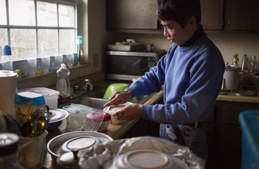 Seh Reh, a Burmese refugee, packs a traditional Kerenni lunch prepared by his wife before heading to work at the Perdue Farms processing plant. Seh Reh is the sole provider for his wife and four children, Kerenni refugees who were resettled in Bowling Green in 2009. The family relies on food subsidies from SNAP to make ends meet. Photo by Leanora Benkato/HERALD