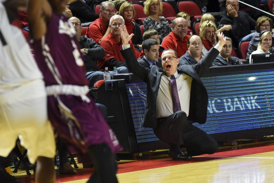WKU's head coach Ray Harper throws his arms up in celebration during the Hilltopper's 86-84 win over Eastern Kentucky University on Tuesday at Diddle Arena.