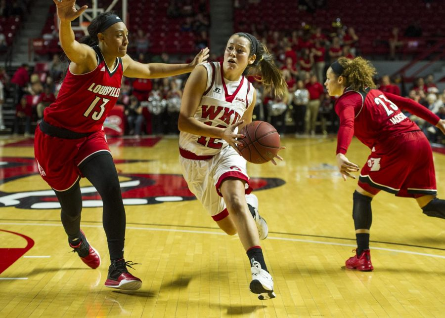 WKUs+guard+Kendall+Noble+%2812%29+drives+to+the+basket+past+Louisville+forward+Cortnee+Walton+%2813%29+during+the+Lady+Toppers+71-69+win+Saturday+at+E.A.+Diddle+Arena.