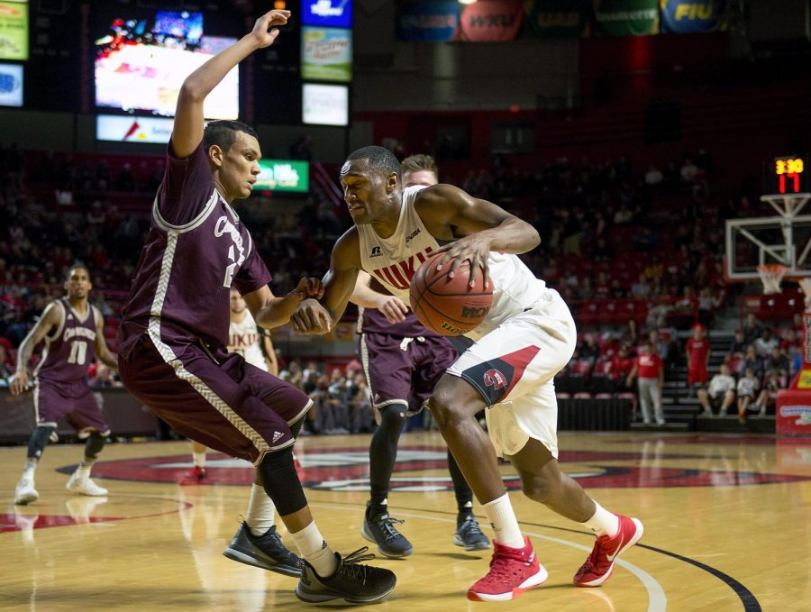Redshirt senior forward Nigel Snipes (21) drives past Campbellsville freshman guard, Hagen Tyler (24), during the game at Diddle Arena. Snipes made the most points that night, with 24 points and three rebounds. Matt Lunsford/HERALD