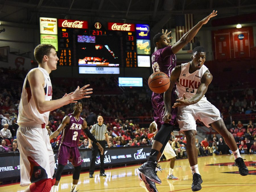 WKUs guard Fredrick Edmond (25) passes around Eastern Kentucky Universitys forward Anthony Pratt Jr. (33) to forward Ben Lawson (14) during the Hilltoppers 86-84 win Tuesday at Diddle Arena.