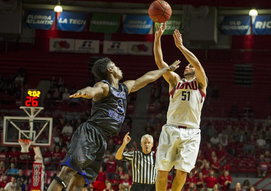 With a hand in his face, Western Kentuckys Chris Harrison-Docks (51) hits a 3-pointer past Kentucky Wesleyans Jordan Jacks (5) defense during Fridays game at E.A. Diddle Arena. The Hilltoppers won the homecoming game 75-68. Nick Wagner/HERALD