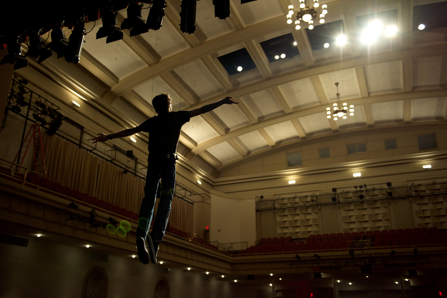 """With the help of his peers who are learning to control the flying wires offstage Greenwood High School senior Joe Moore, 17, practices soaring above the stage for the first time in Van Meter Auditorium on Monday, March 7. """"Flying was the most amazing thing,"""" Moore said of the experience. After three days of training and supervision by professionals, the students were allowed to take the ropes into their own hands. Jennifer King/HERALD"""