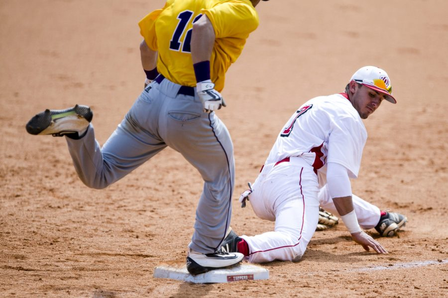 Junior infielder Thomas Peter (7) stretches to keep his foot on the bag to get UA freshman Kevin Donati (12) out at first base during the game on Saturday. The Hilltoppers baseball team takes on the University of Albany Danes at Nick Denes Field in Bowling Green. Mar. 12, 2016. WKU beat UA, 12 - 2. Matt Lunsford/Herald
