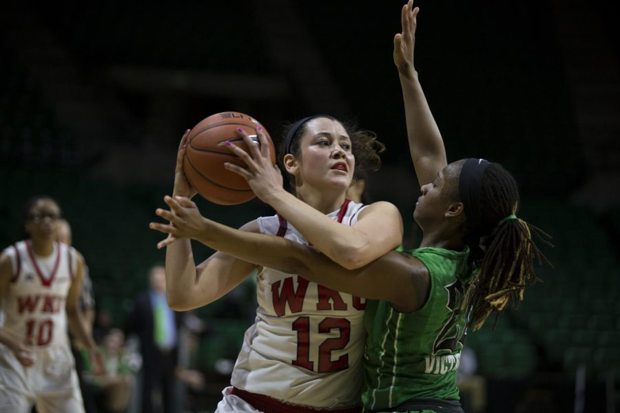 WKU's guard Kendall Noble (12) is closely guarded by Marshall's guard Norrisha Victim (20) during the final seconds of the Lady Topper's 63-66 loss in the quarterfinals of the C-USA tournament Thursday at Bartow Arena in Birmingham, Ala. Mike Clark/HERALD
