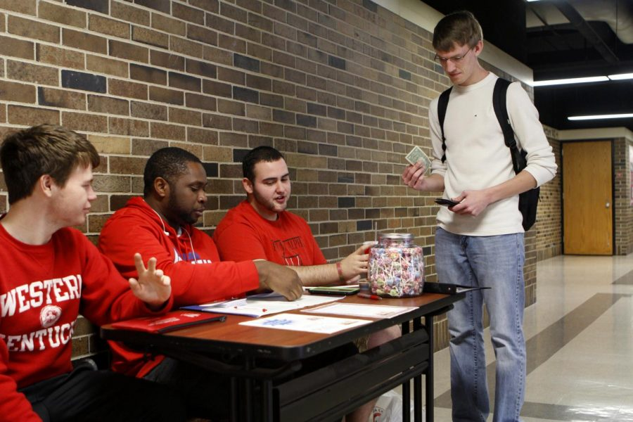 Elizsabethtown sophomore Ethan Smith, Clarksville, Tennessee junior CJ Powell and Bowling Green senior Angelo Rodriguez sit in the Fine Arts Center collecting money for their fraternity's fund- raiser on Monday. Phi Mu Alpha was raising money to help bring music to people with with dementia. KATHRYN ZIESIG/HERALD