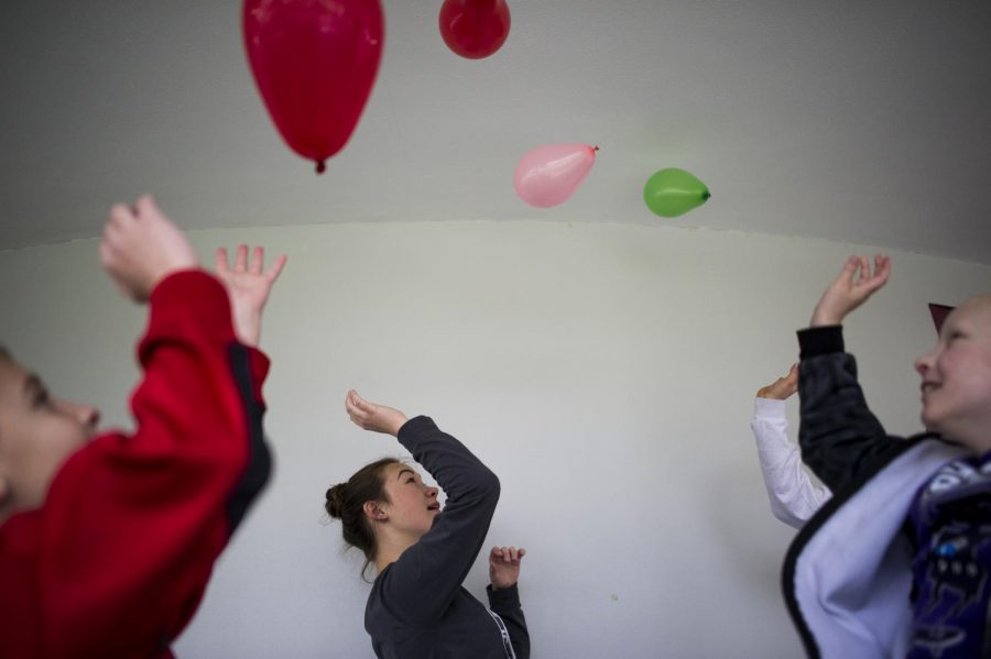 Science Curiosity Investigation campers Peyton West, 8, left, and Lukas Harrison, 9, right, play with balloons with Sara Rastoder, 17, middle, before the start of the day on Wednesday, April 6, 2016 at the Hardin Planetarium. Justin Gilliland/HERALD