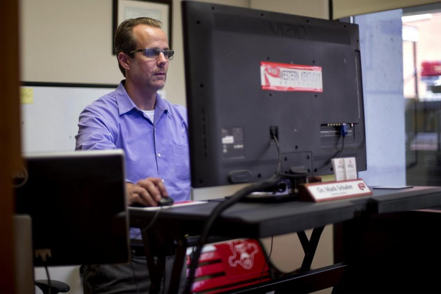 Mark Schafer, professor in the school of kinesiology, recreation and sports, works on his sit-stand work station on Tuesday, Aug. 30 in his classroom at Smith Stadium. Schafer has been working to implement sit-stand work stations in the offices of faculty and staff on WKU's campus. The desks help improve health of people who are in sedentary jobs.