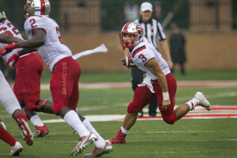 Freshman running back Quinton Baker (3) runs from the defense during the first half of the Hilltoppers