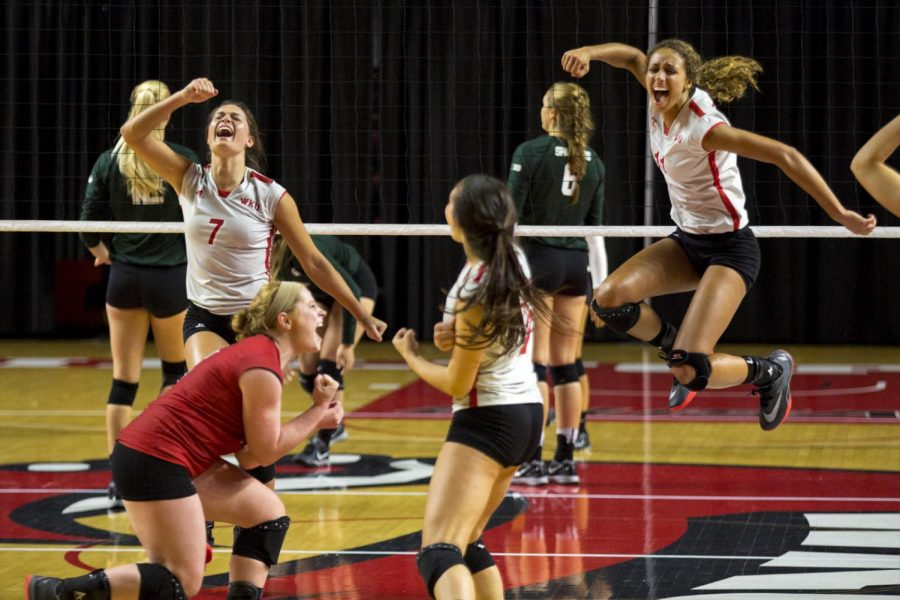 Junior outside hitter Alyssa Cavanaugh (7) and redshirt sophomore middle hitter Amara Listenbee (11) celebrate with their teammates after scoring a point in WKUs 3-2 victory over Michigan State on Saturday, Sept. 10 in Diddle Arena. Ebony Cox/HERALD