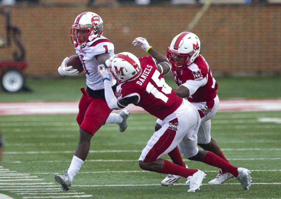 Junior wide receiver Nacarius Fant (1) is driven out of bounds by Miami (Ohio) defensive back Deondre Daniels (15) during WKU's 31-24 victory over Miami (Ohio) on Saturday, Sept. 17 at Yager Stadium in Oxford, Ohio. Matt Lunsford/HERALD