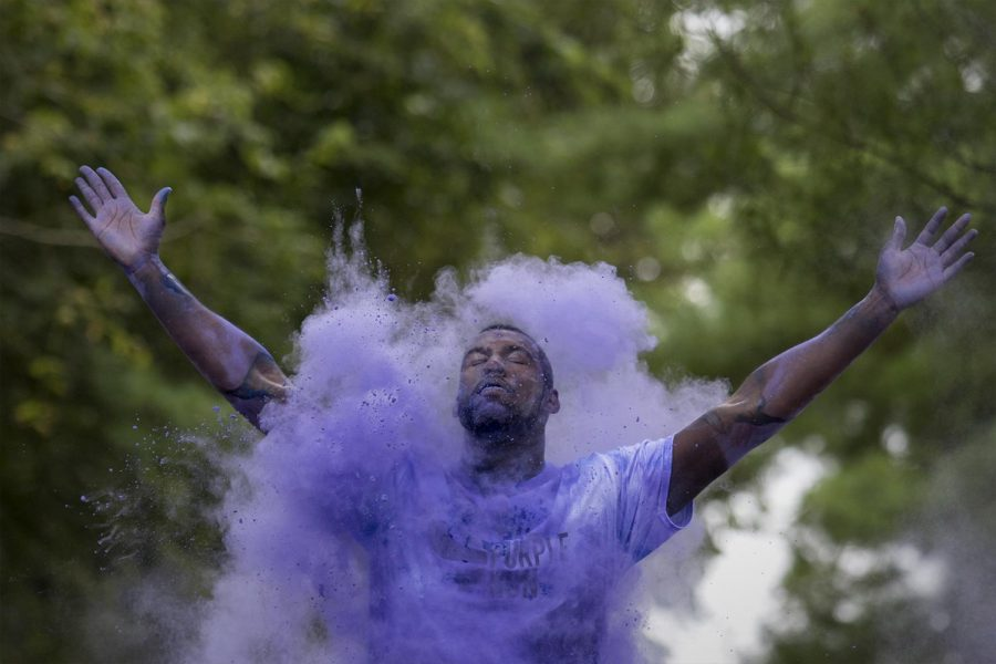 Senior Austin Perkins, 20 of Louisville, raises his hands in the air as he gets ambushed with purple powder during The Purple Run, a 5K walk and run to raise awareness of Alzheimer and to support the Alzheimers Association Saturday, October 1st, 2016 at Kereiakes Park.