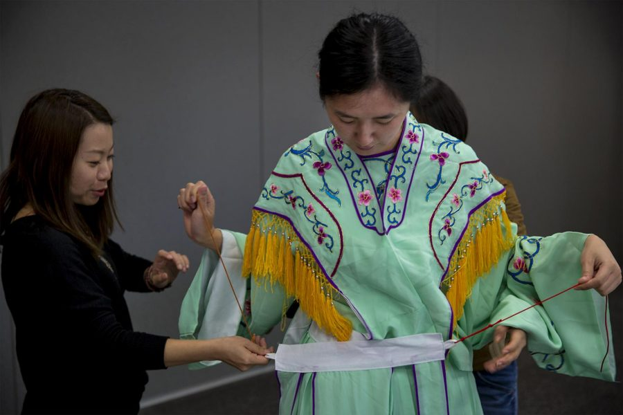 Confucius Institute employee Stella Zhang, 26, gets dressed in traditional Chinese clothing on Oct. 27th, 2016 in the new building for the Confucius Institute building. Brendon O'Hern/ HERALD