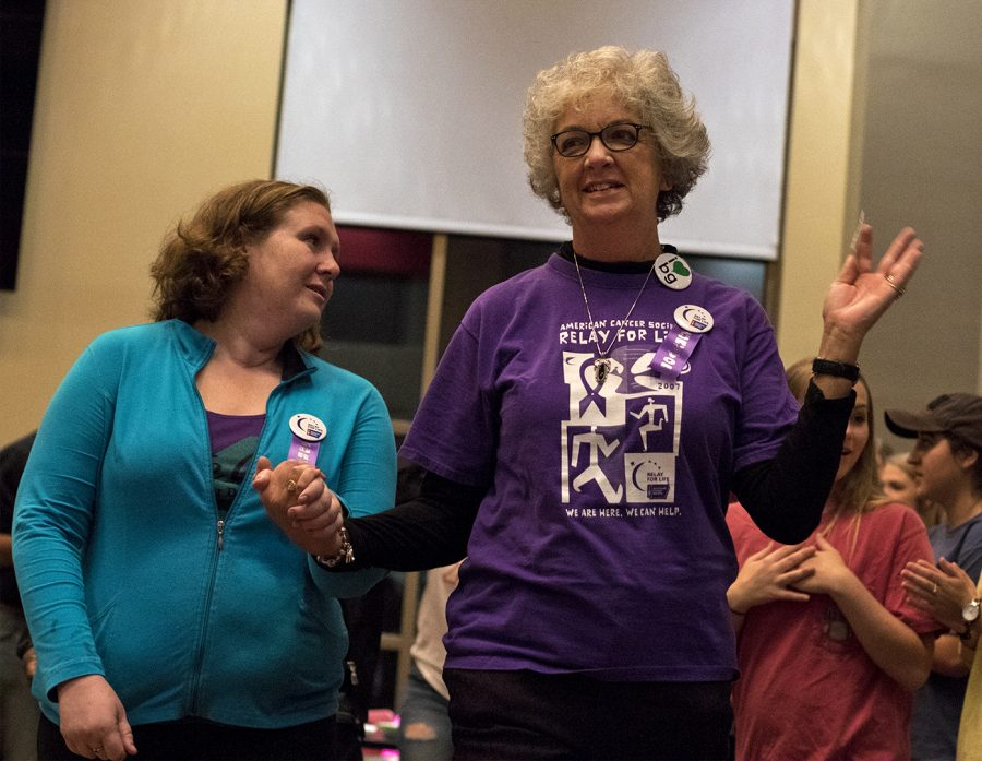 Melissa Nichols of Glasgow, left, and Sue Lynn McDaniel of Bowling Green, two cancer survivors, are cheered on for overcoming their struggle during the American Cancer Society's Relay for Life on Friday, Oct. 14, at Downing Student Union.