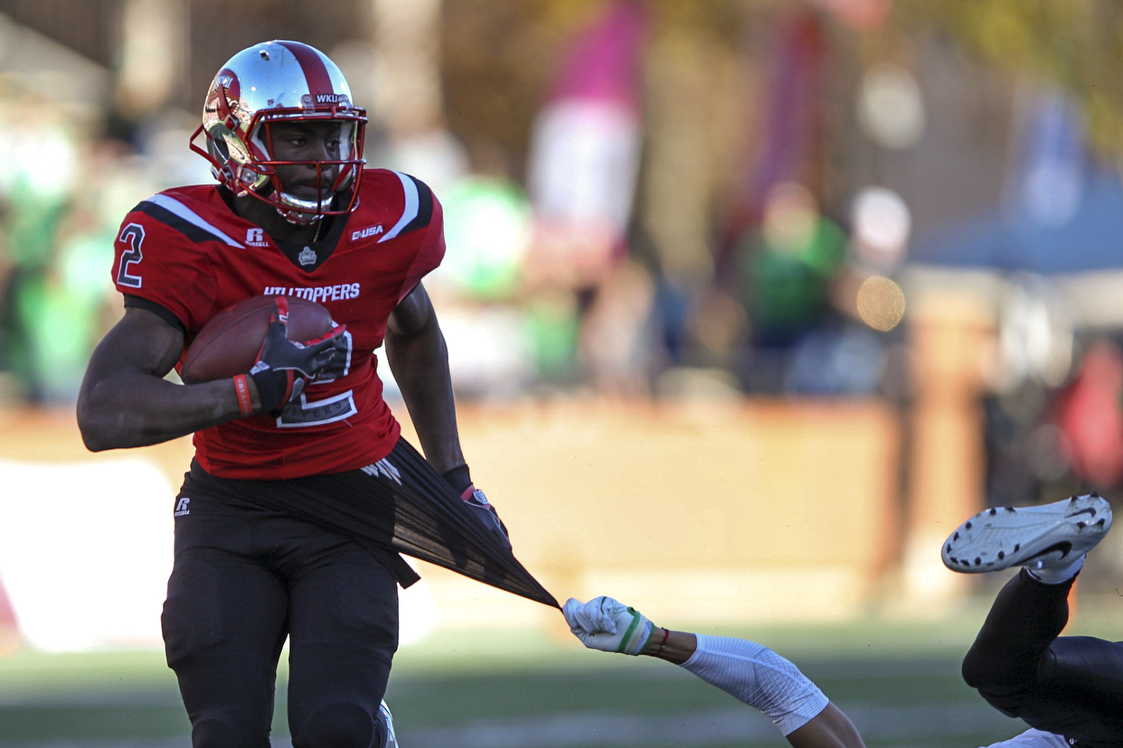 Senior wide receiver Taiwan Taylor (2) carries the ball down field while North Texas defensive back Nate Brooks attempts to stop him during the first half of the WKU football game against North Texas on Nov. 12, 2016 at L.T. Smith Field.