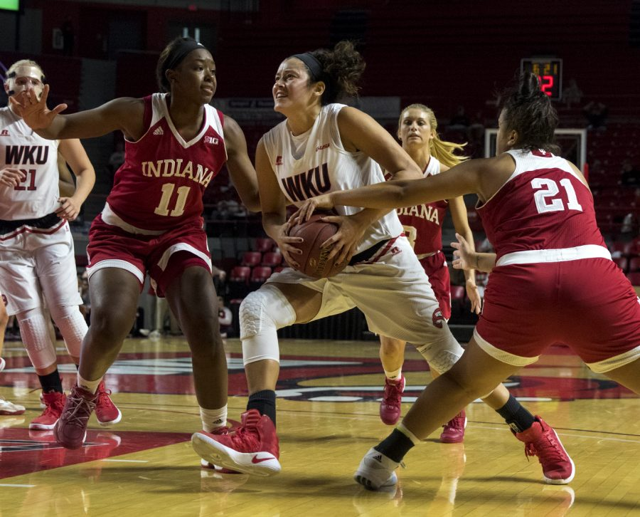 Redshirt+senior+guard+Kendall+Noble+%2812%29+drives+to+the+basket+while+Indiana+University%27s+guard+Karlee+McBride+%2821%29+and+forward+Kym+Roster+%2811%29+guard+her+during+the+Lady+Topper%27s+85-74+win+Nov.+19%2C+2016+in+Diddle+Arena.+Evan+Boggs%2FHERALD