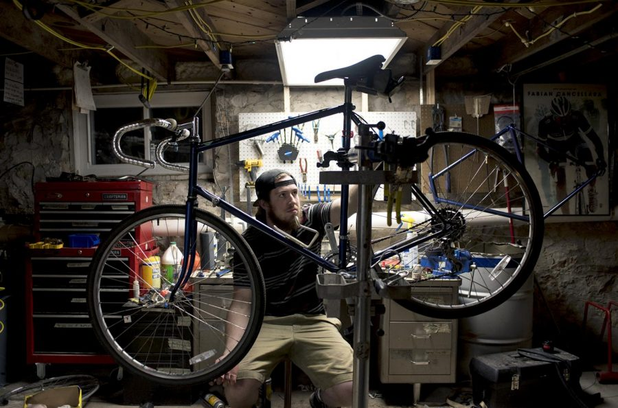 Colton Turley, a student at WKU, adjusts the brakes on a vintage road bike in his shop underneath the Office for Sustainability on Wednesday, Feb. 22, 2017. Turley is the mechanic for the Big Red Bike's program, which repurposes abandoned bikes on campus into rental bikes for students.