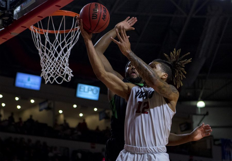 Redshirt senior guard Pancake Thomas (12) puts up a shot as Marshall University forward Ryan Taylor (25) goes to block the ball away during the Toppers 84-79 loss against Marshall University on Saturday, Feb. 11, 2017 in Diddle Arena.