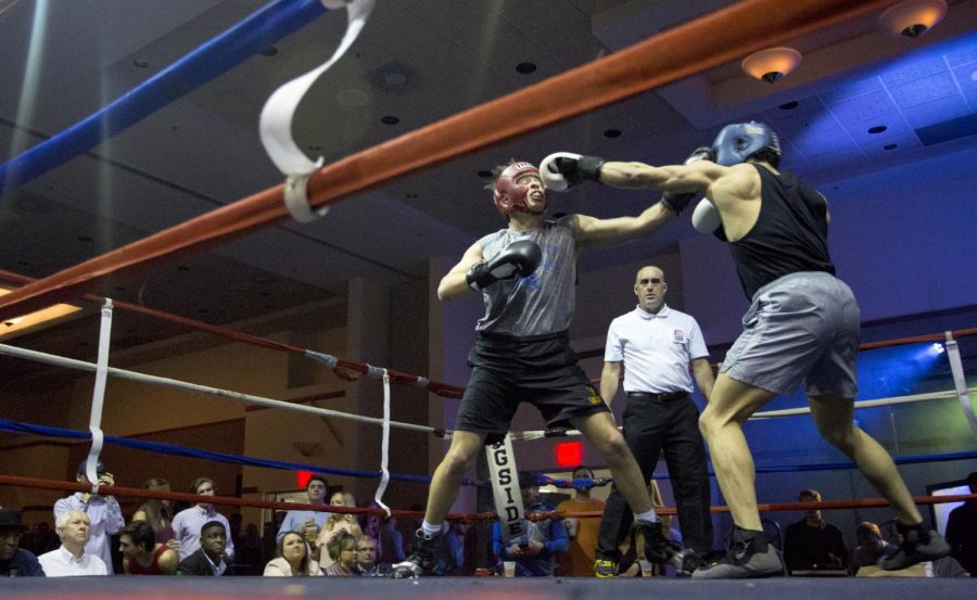 Sumner Franklin (on left), from UK, takes a punch to the face from Miguel Brarzey, from WKU, at the Sigma Chi Fraternity Fight Night in the Sloan Conventions Center on Feb. 10, 2017. Franklin ended up winning the match.