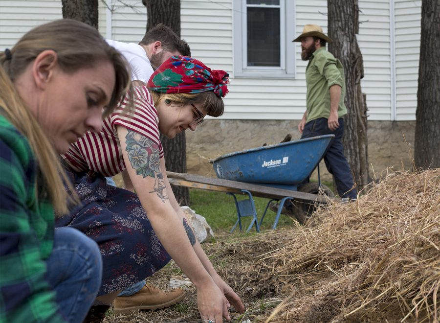 """Melissa Whitley, Executive Director at Hope Harbor, and Alayna Milky, the Crisis Intervention Specialist, apply hay to the potato plants at Hope Harvest. """"I love the joy the produce and working outdoors has brought to clients of all ages. It has given us a new way to engage with volunteers and the community that I never expected,"""" said Whitley."""