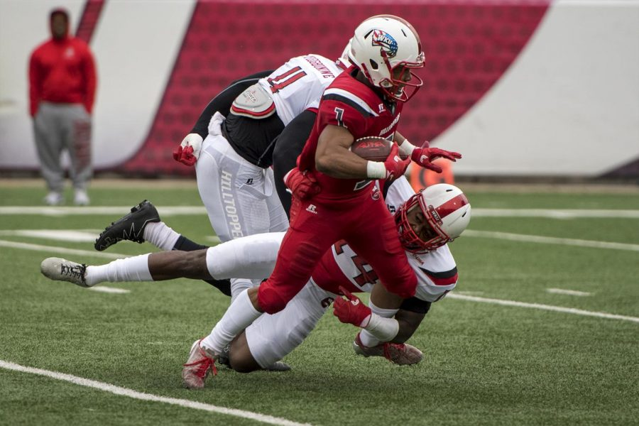 Defensive lineman Tanner Reeves (11) and defensive back Juwan Gardner (14) tackle Wide receiver Jahcour Pearson (1) during the Red and White game on Saturday at L.T. Smith Stadium.