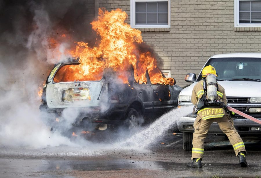 Chris Stafford, 28, of Bowling Green, arrives at the scene of the burning vehicle outside of CampusWalk apartments next by Hilligans. Stafford takes ahold of the fire hose to put out the fire.