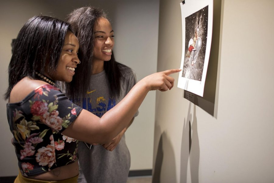 Freshmen Charity Davis (left) and Shante Parker (right) look at one of Emily Hendricksen's collages in the gallery Tuesday April 18, 2017 in DSU . Hendricksen, along with artist Jack LeSieur, spoke about the work they have displayed in DSU during the Artists Talk session.