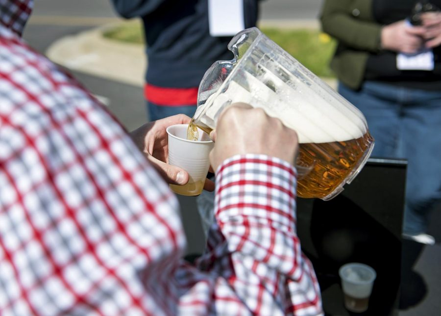 A volunteer pours local beer into servings at Red White and Brew April1, 2017 at the WKU Alumni Center. Individuals who perched tickets got 10oz pours of locals beers and a free meal.