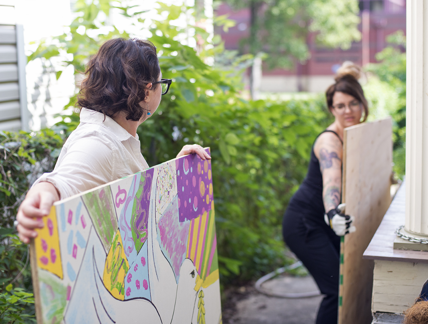 Amanda Crawford and Courtney Davis transport a painted mural to FFOYA house on Tuesday, 2017. The mural will be displayed in the FFOYA house gallery, before being installed in the Barren River Area Safe Space garden.LYDIA SCHWEICKART/HERALD