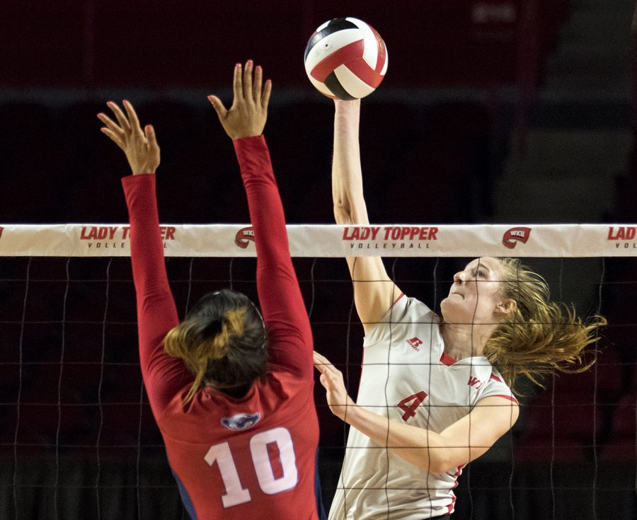 Junior outside hitter Rachel Anderson (4), spikes the ball as rightside hitter Abbi Reid (10) attempts to block during WKU's match against Florida Atlantic on Thursday, September, 22nd, 2016, in Diddle Arena.