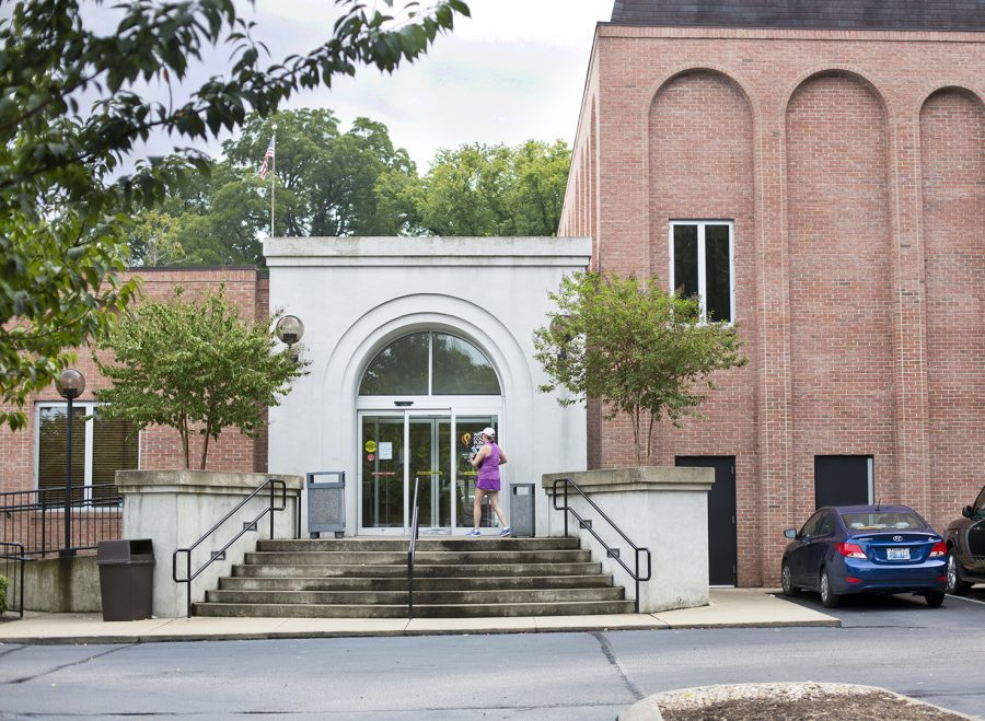 A woman approaches the entrance of Warren County Public Library on State Street, reading a sign regarding how all branches of the library will be closed on Monday Aug. 28.