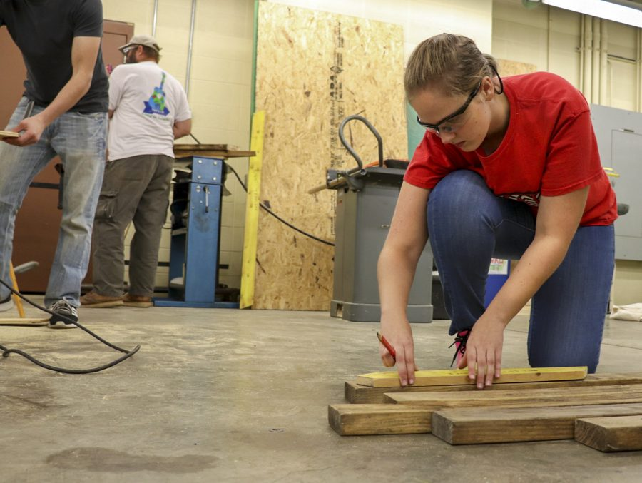 Radcliff sophomore Allison Hohenstein prepares lumber to be cut while building trusses for sheds to go to families in Bowling Green. This was Hohenstein's first time participating in the WKU chapter of Habitat of Humanity, who had their beginners' build Sept. 7.