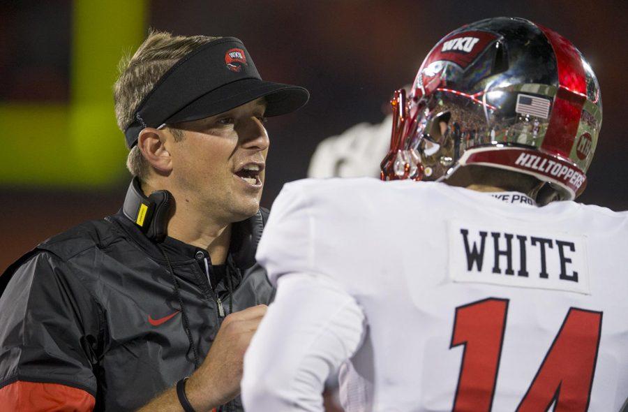 WKU head coach Mike Stanford talks to senior quarterback Mike White (15) on Sept. 9 during WKU's game against University of Illinois.