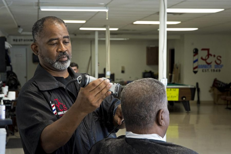 """Junius Carpenter cuts a clients hair Tuesday at JCs Barbershop. Carpenter and his wife now plan to open a """"barbershop college"""" to teach others the ways of barbering. """"We look at it as our semi-retirement job, he said. This is like the pinnacle of our profession: to teach all the wisdom and knowledge we've learned over the years."""""""